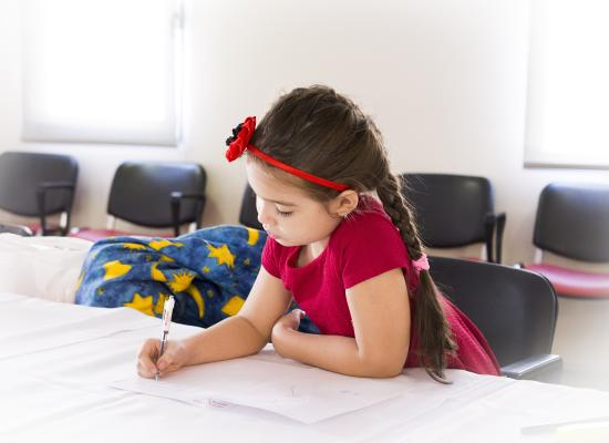 young girl sitting at desk and writing on paper