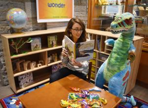 Lady reading in childrens play area to a toy dinosaur